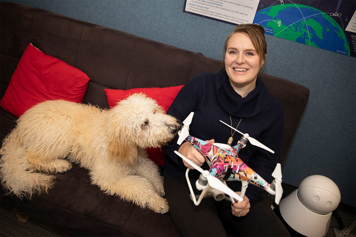 Jordan sitting with her dog, holding a drone
