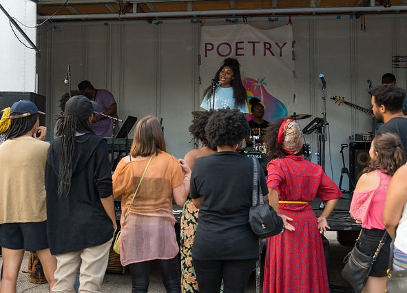 A poet reading on stage in front of a crowd of people