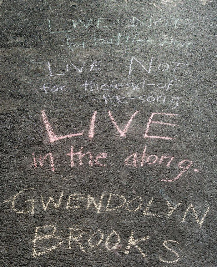 """sidewalk chalk on the street that says """"Live not for Battles Won. Live not for The-End-of-the-Song. Live in the along. Gwendolyn Brooks"""""""