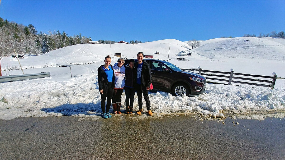 Andy Cohen and three women standing in front of their car stuck in the snow